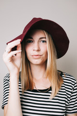 Young woman looking into the camera wearing a hat