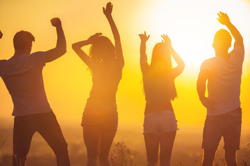 The four people dancing on the background of the bright sunset