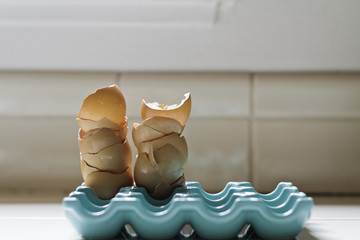stack of broken eggshells on blue holder
