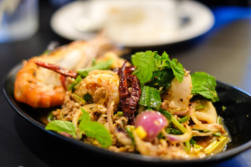 Big shrimps and squids and spicy minced pork mixed together with various herbs and vegetables including dried chilli served on black plate, for thai food background or texture.