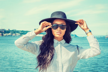 Young American Woman with long hair traveling in New York in summer, wearing white striped shirt, black sun hat, sunglasses, standing by Hudson River, hand touching hat. Bridge on far background,