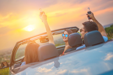 The happy people sit in a cabrio on the bright sun background