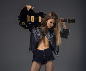 Beautiful Woman With Guitar In Rock Band Isolated On Gray Background