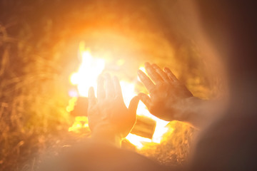 The person warming hands above the bonfire. evening night time