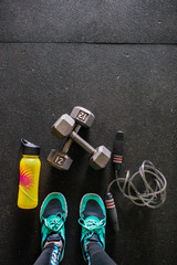 A woman looking down at her fitness gear
