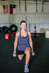Attractive sporty young athletic woman using free weights