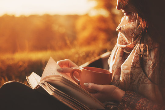 a woman sits near a tree in an autumn park and holds a book and a cup with a hot drink in her hands. Girl reading a book