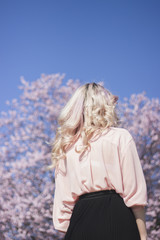 Young woman looking at big cherry blossom tree