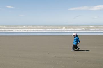 Toddler walking on beach, New Zealand.