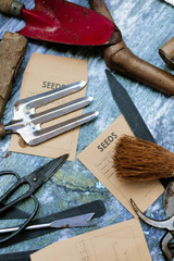 Overhead shot of old-fashioned gardening tools on table with seeds envelopes
