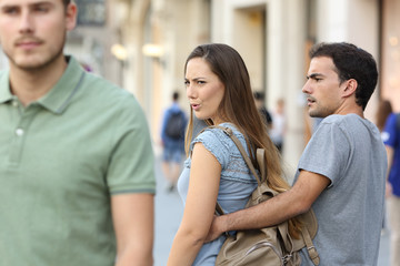 Disloyal woman looking another man and her angry boyfriend