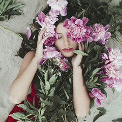 Portrait of a beautiful young woman with peonies flowers