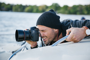 Portrait of Male Photographer Shooting With Digital DSLR Camera on Boat