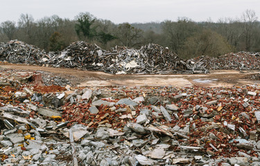 Piles of broken cement, wood and bricks at demolition site for future building construction