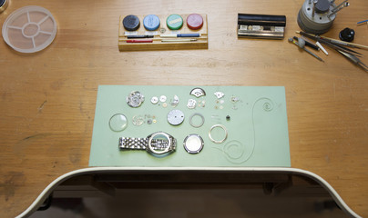 Parts of deconstructed watch lying on clockmaker table
