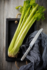 Bouquet of fresh celery in vintage box on an old wooden background. Selective focus. Top view. Copy space.
