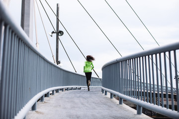 Back view of a young african american woman running on a bridge in the city.