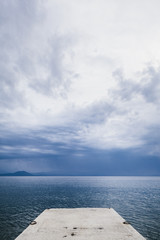 Stone pier and stormy weather above the Aegean sea