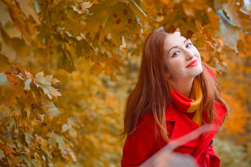 Cute and nice young beautiful woman in a red casual coat and red-yellow scarf walks in autumn city park. Pretty view of walking woman outside