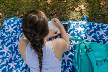 Aerial view of a young lady is studying on a blanket