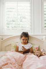Young cute girl reading in bed for homeschool