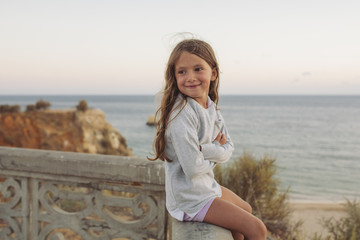 Child sitting on a wall above sea.