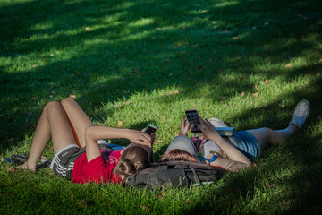 Young woman lying on the grass is browsing her cellphone