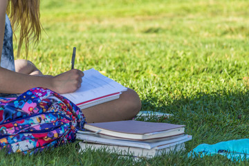 Hand of a young woman is studying outdoor on grass