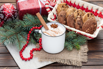 eggnog cocktail in  mug arranged with christmas decoration and cookies box on wooden table