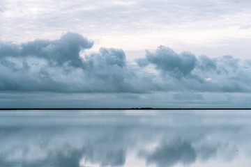 Reflection of sky and clouds with a strip of land in the middle in Iceland