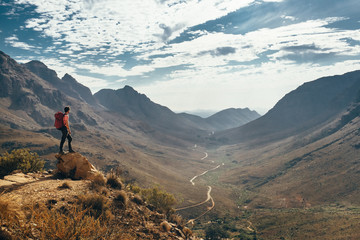 Hiker on an outcrop taking in a mountainous valley view