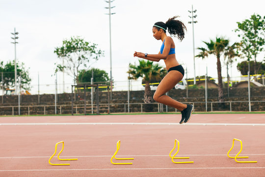 Young woman jumping over obstacles on an athletics track.
