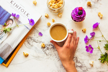 Kazakhstan, Almaty - 26 AUGUST, 2017: Popular magazine Kinfolk, popcorn, woman's hand with cup of coffee, wild flowers and violet cupcake. Top view, life style