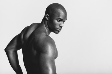 Rear view black and white shot of young man with muscular build looking over shoulder