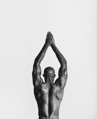 African man standing with his hands joined above his head