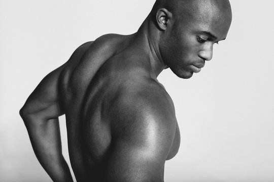 Young african man with muscular build looking down