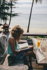 Woman reading a book near beach