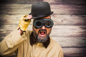 Man with beard, bowler, raincoat and some strange futuristic glasses over wooden background