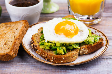 Avocado egg sandwich with whole grain bread on wooden background. Copy space