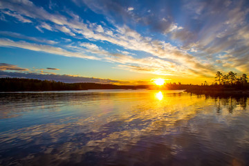 Russia. Karelia. Ladoga lake. Reflection in the water of the sunrise.
