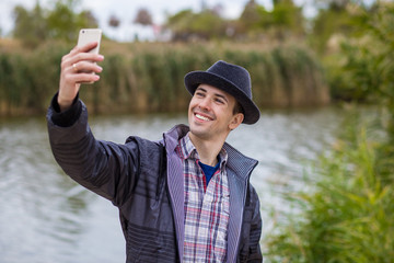 Young happy man taking selfie in fashionable clothes on the river bank