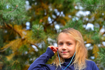 girl in headphones with phone in the forest with her hair down