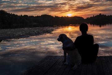 Силуэты собаки и девушки на фоне заката.
