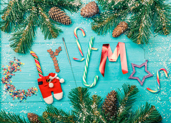 Toned photo of blue table with spruce branches, word Christmas