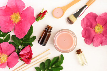 Herbal extracts preparation natural cosmetic products. Pink fresh wild rose flowers and leaves, bottles and jars, top view.