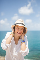 Portrait of a cute looking woman holding her hat on a windy day