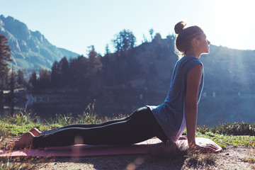 Fit young happy traveling girl practicing yoga outdoor in the stunning mountain wilderness in front of amazing cold lake at sunrise. Calmness and relax, female happiness.