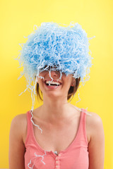 Happy young woman hiding her eyes with blue party decoration.