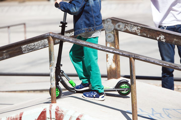little boy on scooter board in the ramp of the skate park / young skateboarder training on the skate park ramp