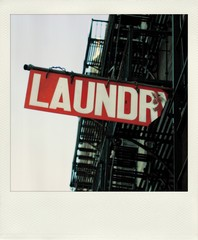 Old  snapshot print of a laundry sign hanging under a fire escape